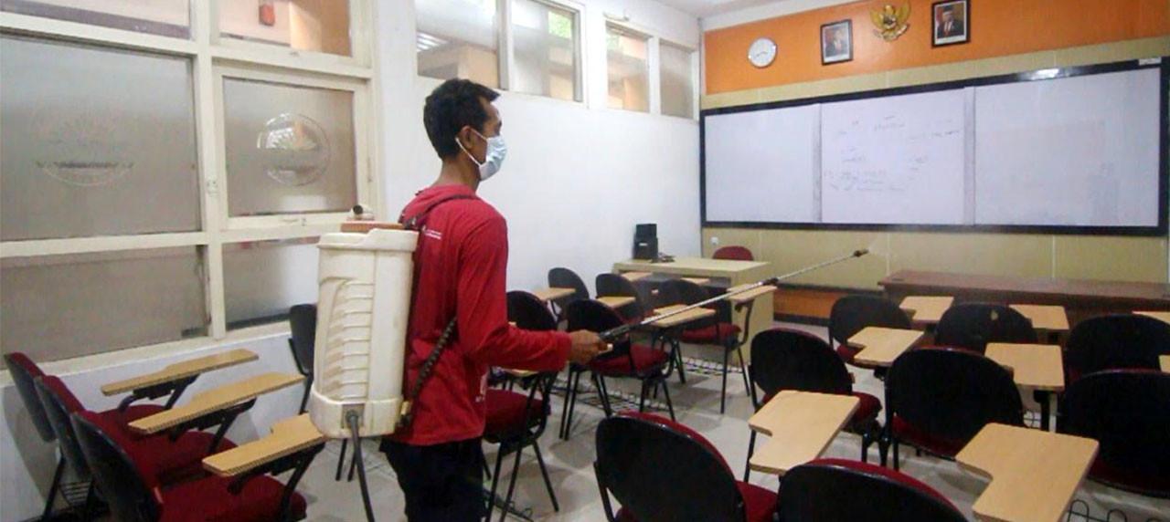 Petugas UISI sedang menyemprotkan disenfektan di kelas.
