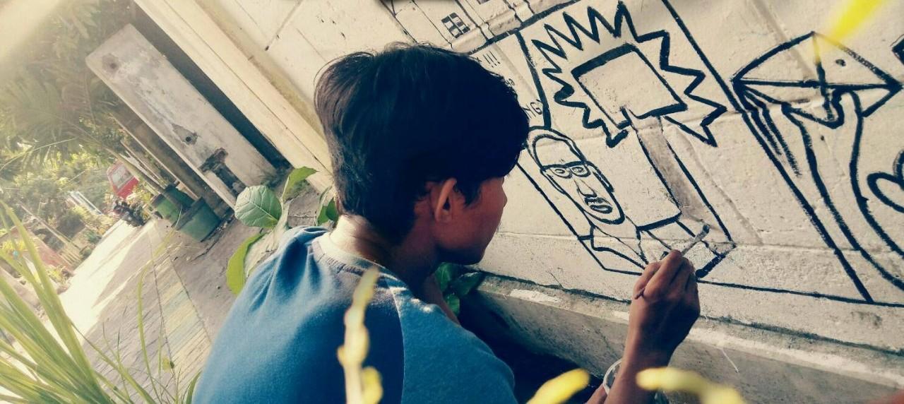 Mahasiswa DKV UISI sedang melukis mural di dinding awikoen tama