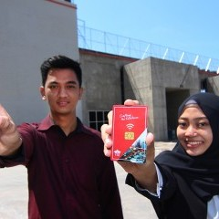 Mahasiswa memegang smart card di depan bangunan kampus