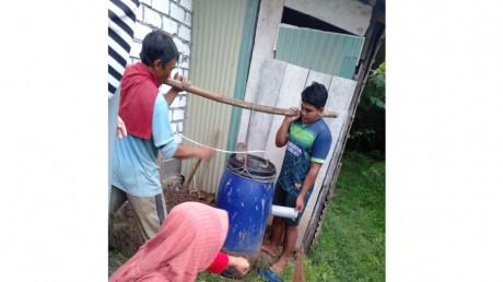 Febrian, anggota PENGMAS HIMATRIAN UISI 2021, bersama warga memasang bioreaktor biogas.