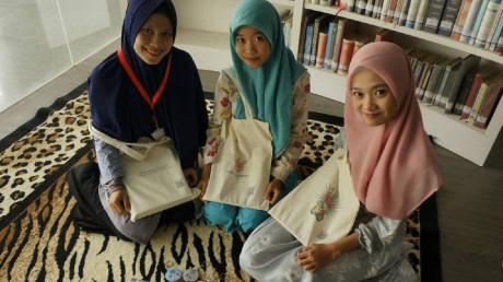Tim mahasiswa Informatika yang menunjukkan produk  Belum Nemu berupa tote bag dan gantungan kunci