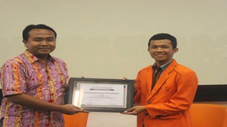 Pemberian sertifikat penghargaan oleh ketua pelaksana kepada Budiana Nur Rohmad selaku pemateri
